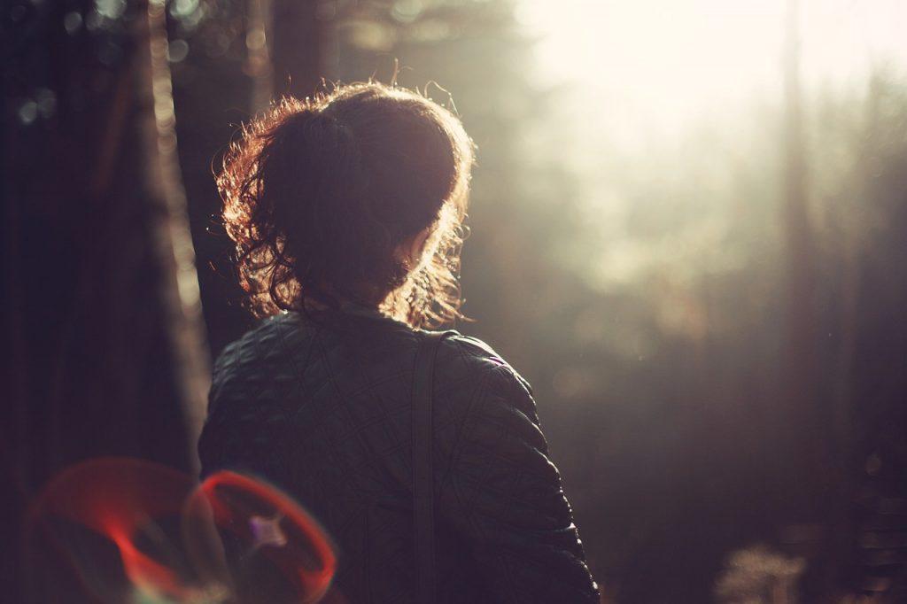 Lady sitting in woodland, thinking.